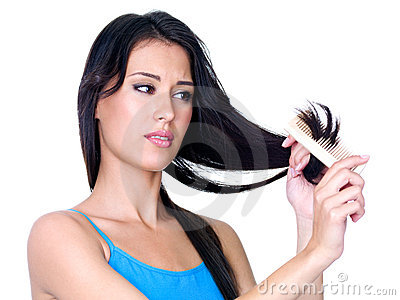 Woman combing ends of her hair