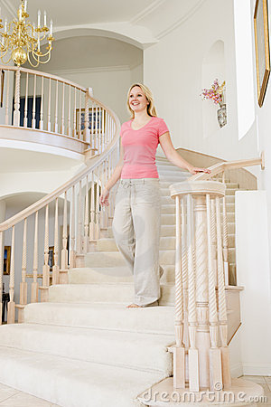 Woman coming down staircase in luxurious home