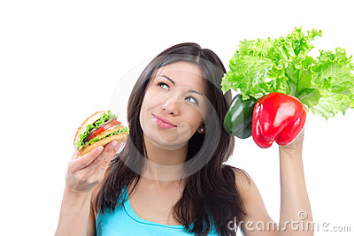 Woman comparing burger and fresh peppers salad