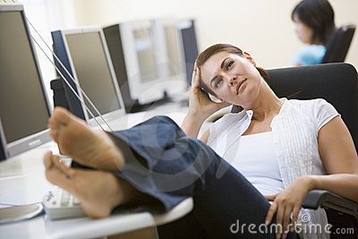 Woman in computer room with feet up thinking