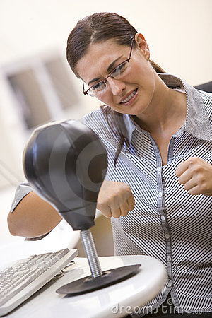 Woman in computer room using small punching bag