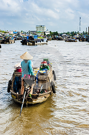 Woman with concal hat driving her machine boat to floating marke