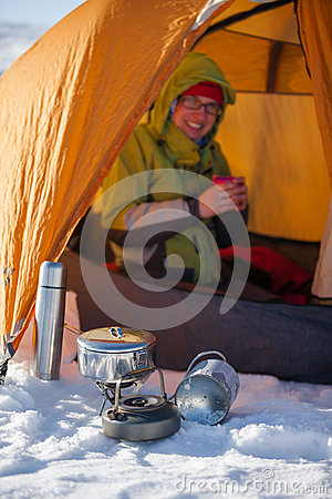 Woman cooking outside tent in wintertime Stock Photo