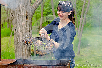 Woman cooking over a BBQ reacting in horror Stock Photo