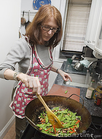 Woman cooking with wok