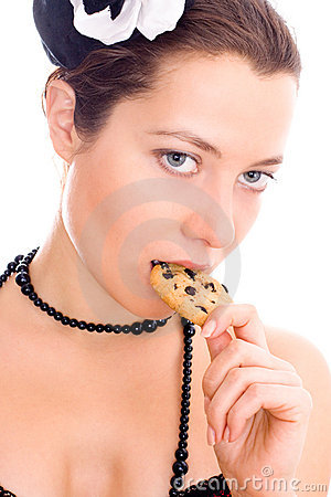 Woman in corset and little hat eating cookie