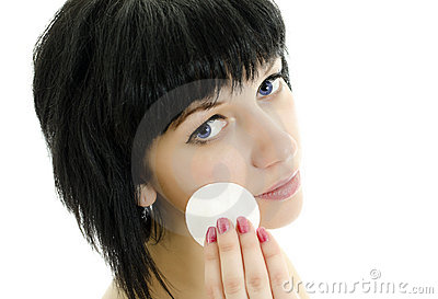 Woman with cotton swab cleaning her face.