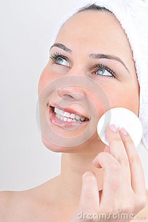Woman with cotton swab cleaning her face