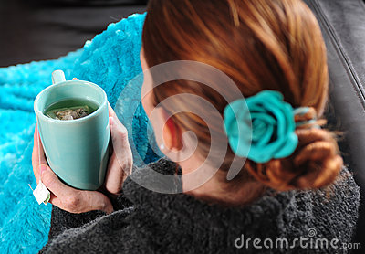 Woman on couch with blanket and cup of tea