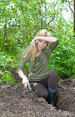 Woman couch a garden-bed with the first sprouts