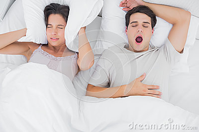 Woman covering ears with a pillow while her partner is snoring