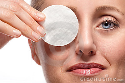 Woman covering eye with cotton pad