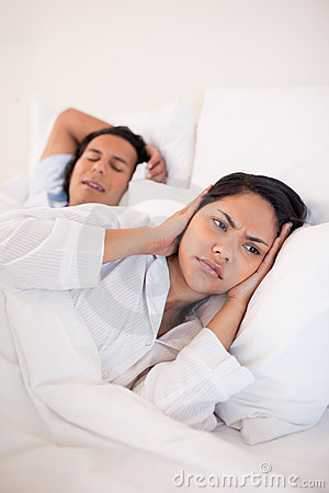 Woman covering her ears to block her boyfriends snoring