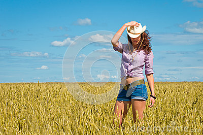 A woman in a cowboy hat and jeans shorts