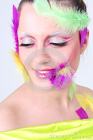 Woman with creative make-up and feathers
