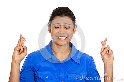 Woman crossing fingers wishing and praying for miracle