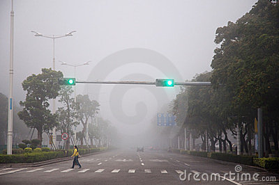 woman crossing road in fog Editorial Stock Photo