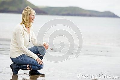 Woman crouching on beach