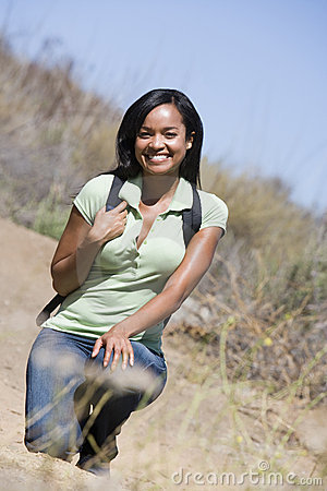 Woman crouching on beach path smiling