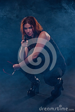 Woman crouching down aiming a gun