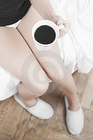Woman with a cup of coffee and slippers