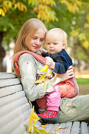 Woman and cute baby with leafs sitting on bench