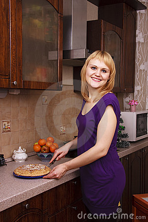 Woman cutting hot apple pie at kitchen
