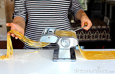 Woman cutting pasta dough on the machine at home