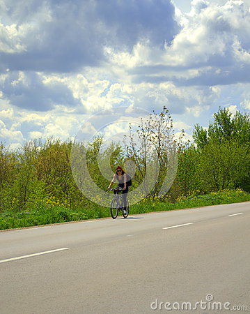 Woman cycling spring road Stock Photo