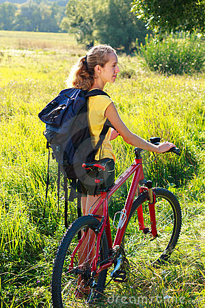 Woman cyclist with bike and backpack