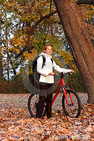 Woman cyclist with bike and backpack in morning