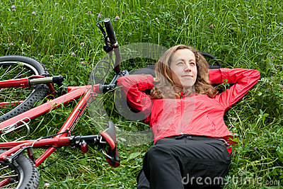Woman cyclist relaxes lying among the green grass