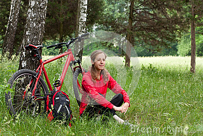 Woman cyclist relaxing among the green of nature