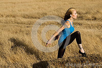 Woman in Dance Pose in a Field of Grass