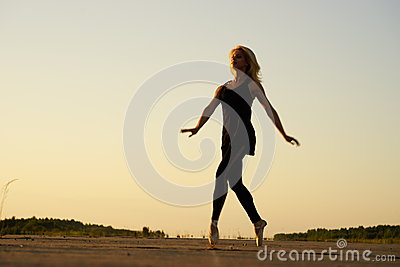 Woman dancer posing on concrete road
