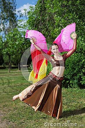 Woman dances with pink veil fans