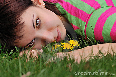 Woman with dandelion lying on green grass