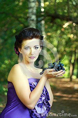 Woman dark blue grapes