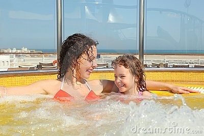 Woman with daughter both smiling in hot tub
