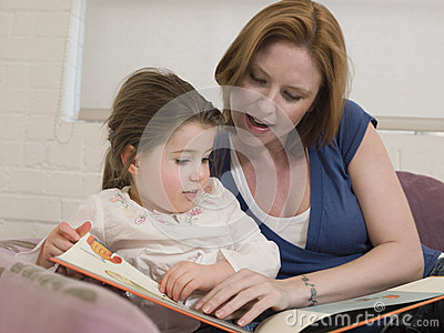 Woman And Daughter Looking At Picture Book