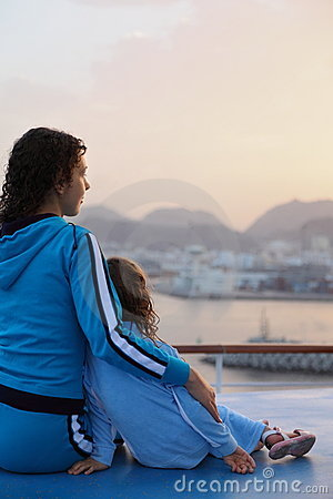 Woman and daughter sitting on deck of cruise ship