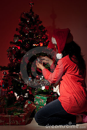 Woman decorate Christmas tree in night
