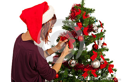 Woman decorate tree with ribbons