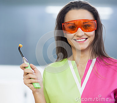 Woman dentist holding a dental polymerization lamp