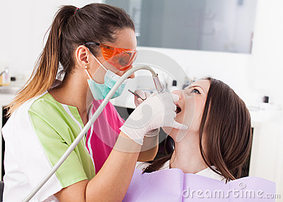 Woman dentist working with the driller