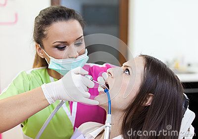 Woman dentist working on her patient s teeth