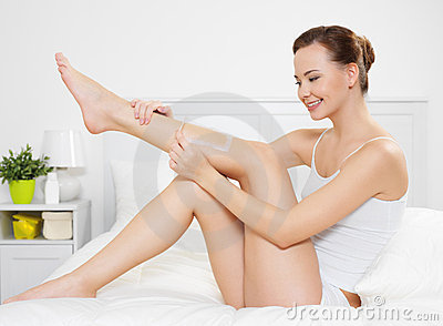 Woman depilating skin on legs by waxing
