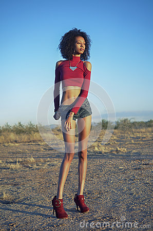 Woman in desert location wearing denim shorts.