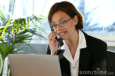 Woman at desk with laptop computer and phone