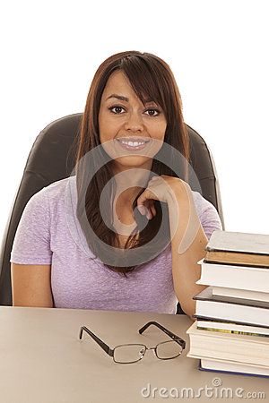 Woman at desk with a stack of books smiling